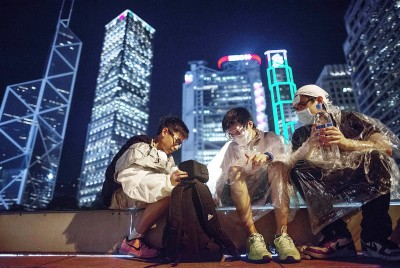Protesters sit on top of a parking ramp in the Central District on Monday in Hong Kong.