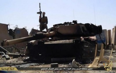 An Islamic State fighter stands on top of a US-made M1 Abrams tank.