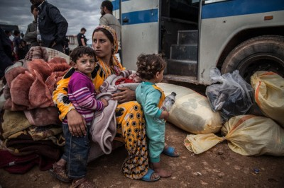 In Yumurtalik, Turkey, a Syrian Kurdish family waited to be taken to a Turkish shelter after fleeing shelling. Credit Bryan Denton for The New York Times