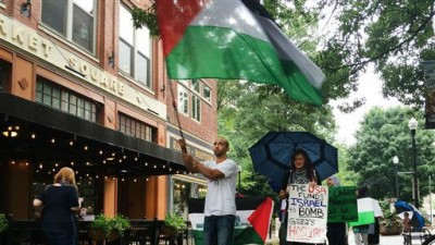 Ahmad Abuleil waves a Palestinian flag as he leads Amira Sakalla, head of University of Tennessee Students for Justice In Palestine, and others in a march in Knoxville, Tenn. on Friday, July 18, 2014 (photo credit: AP/Knoxville News Sentinel, Megan Boehnke)