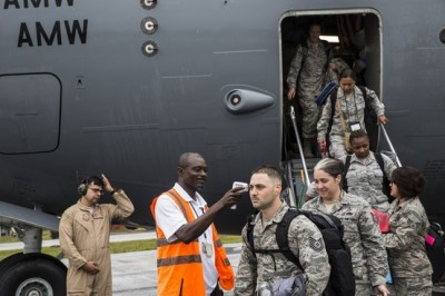 A local health official checks the temperature of a newly arrived U.S. soldier at the airport in Robertsfield, Liberia, as other troops disembark. Glenna Gordon for The Wall Street Journal