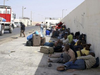 Sudanese workers rest on the ground as they wait for Egyptian visas, next to the Libyan-Egyptian border crossing in Musaid