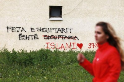 A woman walks past a wall with graffiti at the University of Pristinia September 26, 2014.