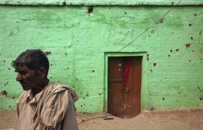 An Indian villager stands next to the wall of a house that locals say was damaged by firing from the Pakistan side of the border at Arnia village