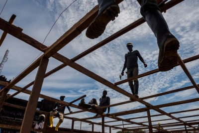 While a United States delegation was visiting, Liberian workers were constructing the frame for a 300-bed Ebola treatment center Wednesday in Monrovia. Credit Daniel Berehulak for The New York Times