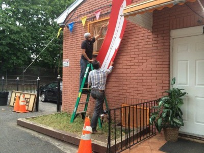 A sign is removed from the front of the Muslim American Society of Staten Island, located in Dongan Hills