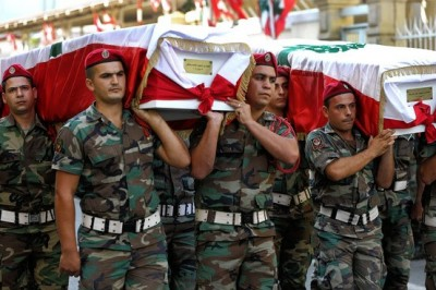 Lebanese army officers carry the coffins of two soldiers killed by a roadside bomb, in a funeral procession last month at Beirut's army hospital. Associated Press