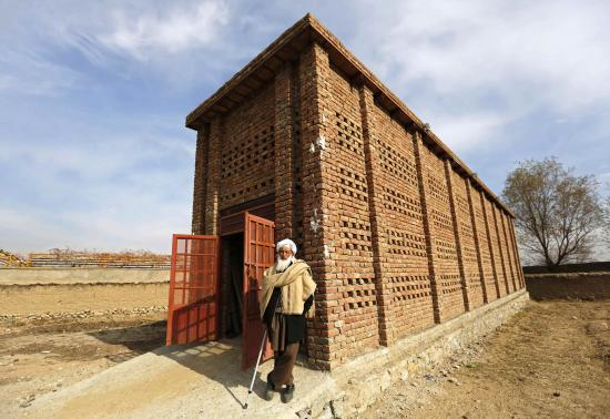 Afghan farmer Mohammad Malik stands outside his grape pitfall which was build by USAID project in Parwan