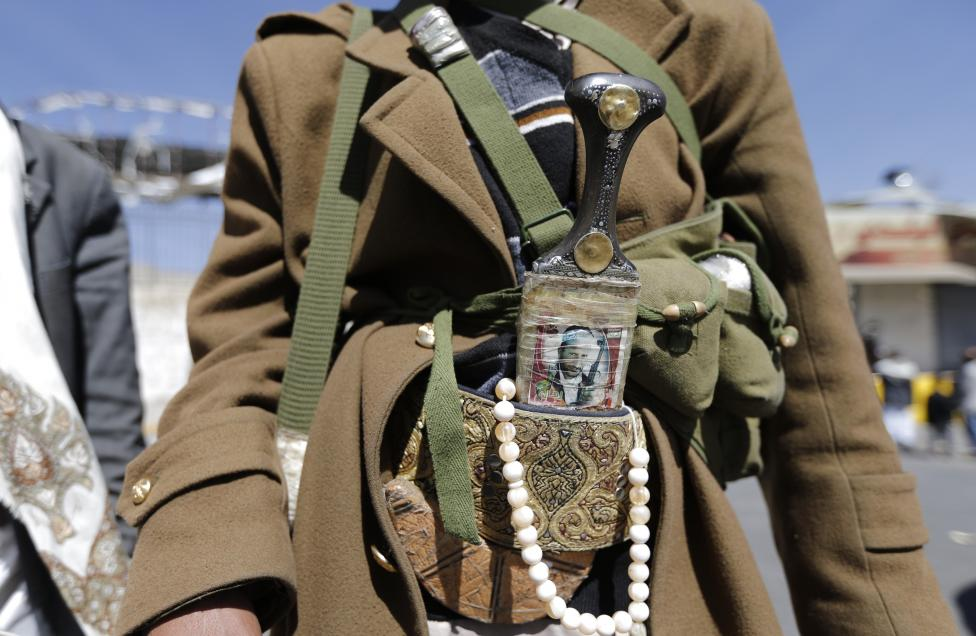 A Houthi fighter wears a traditional dagger with a picture of a slain comrade on it as he poses for a photo in Sanaa