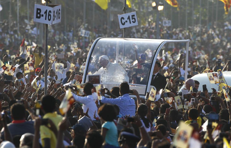 Pope Francis waves to Catholic faithful as he arrives to lead mass in Colombo