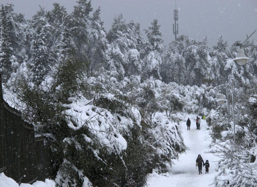 People walk through a park as snow falls in Jerusalem