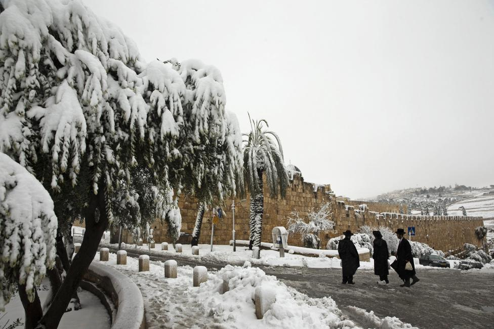 Ultra-Orthodox Jewish men stand on a snow-covered street outside Jerusalem's Old City