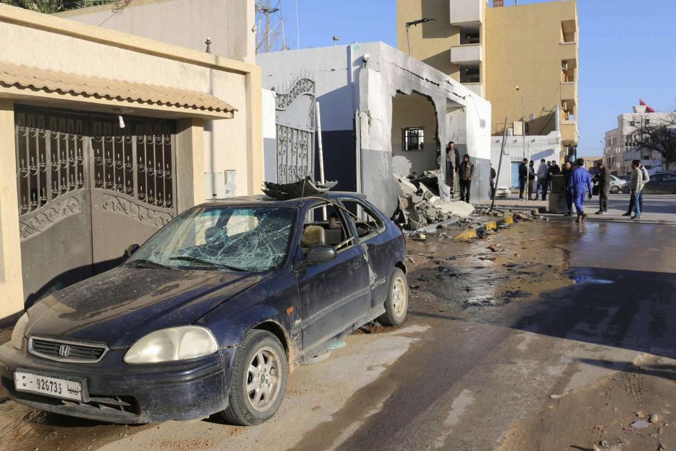 Civilians and security personnel stand at the scene of an explosion at a police station in the Libyan capital Tripoli