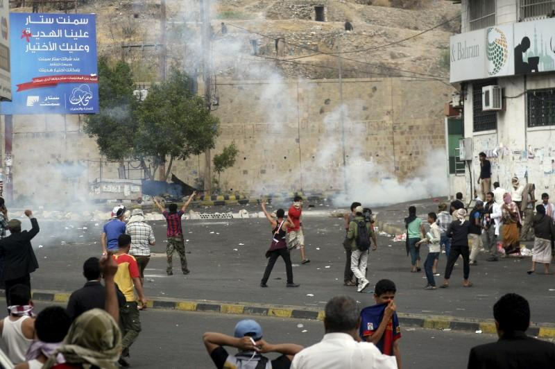 Pro-Houthi police troopers use tear gas to disperse anti-Houthi protesters in Yemen's southwestern city of Taiz