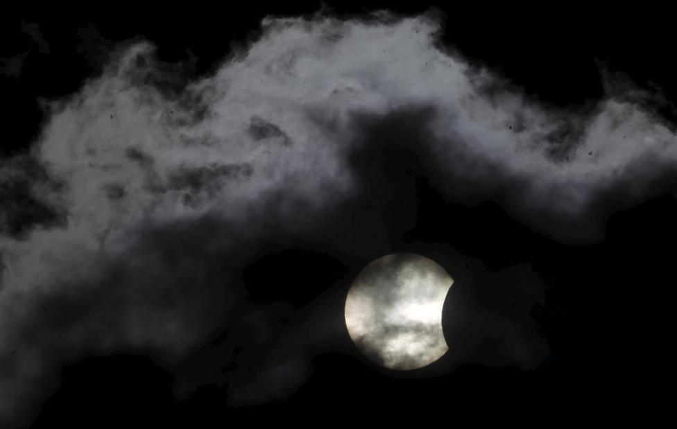 A partial solar eclipse is seen through clouds in Sarajevo