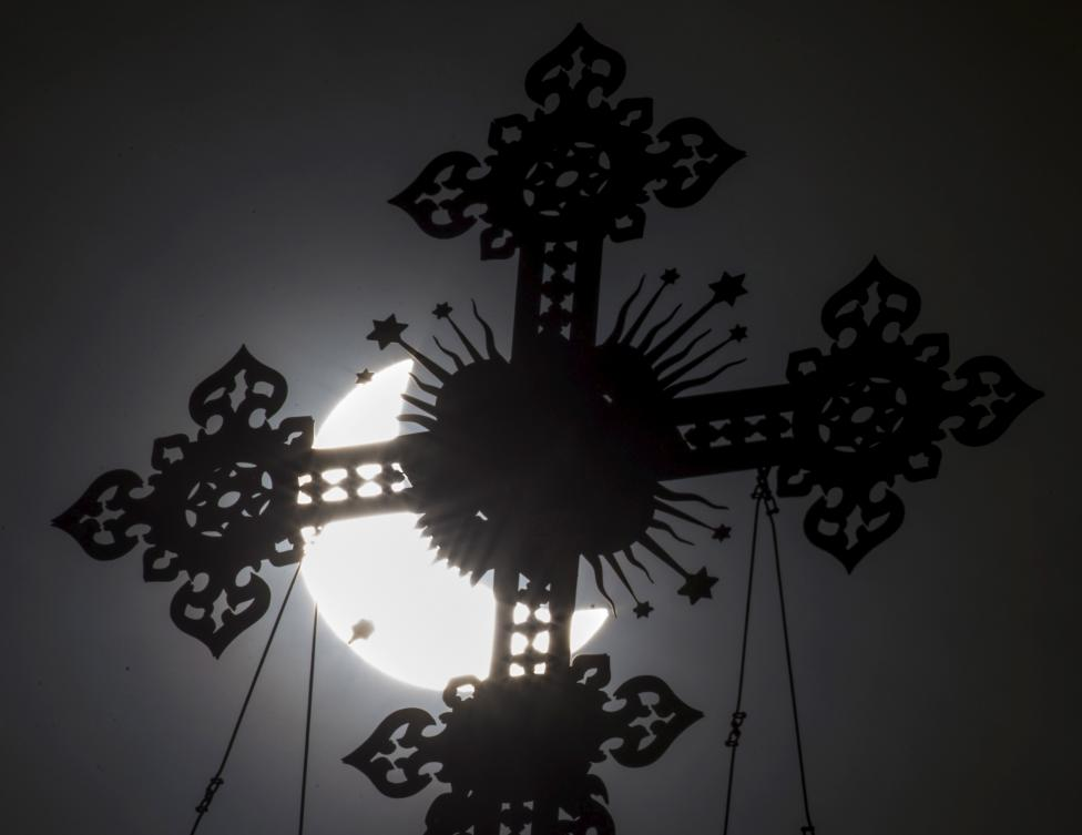 A cross on the dome of the Cathedral of Christ the Saviour is seen during a partial solar eclipse in Moscow