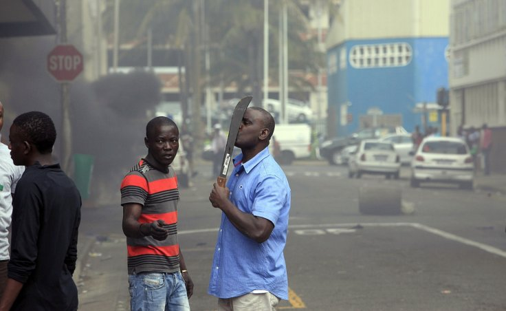 A foreign national holds a machete to protect himself after clashes broke out between a group of locals and police in Durban, South Africa, on 14 April 2015