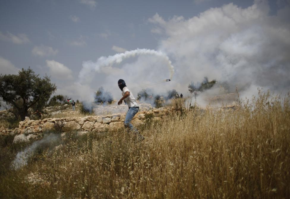 A protester returns a tear gas canister fired by Israeli troops during clashes following a protest marking Palestinian Prisoners' Day near Ramallah