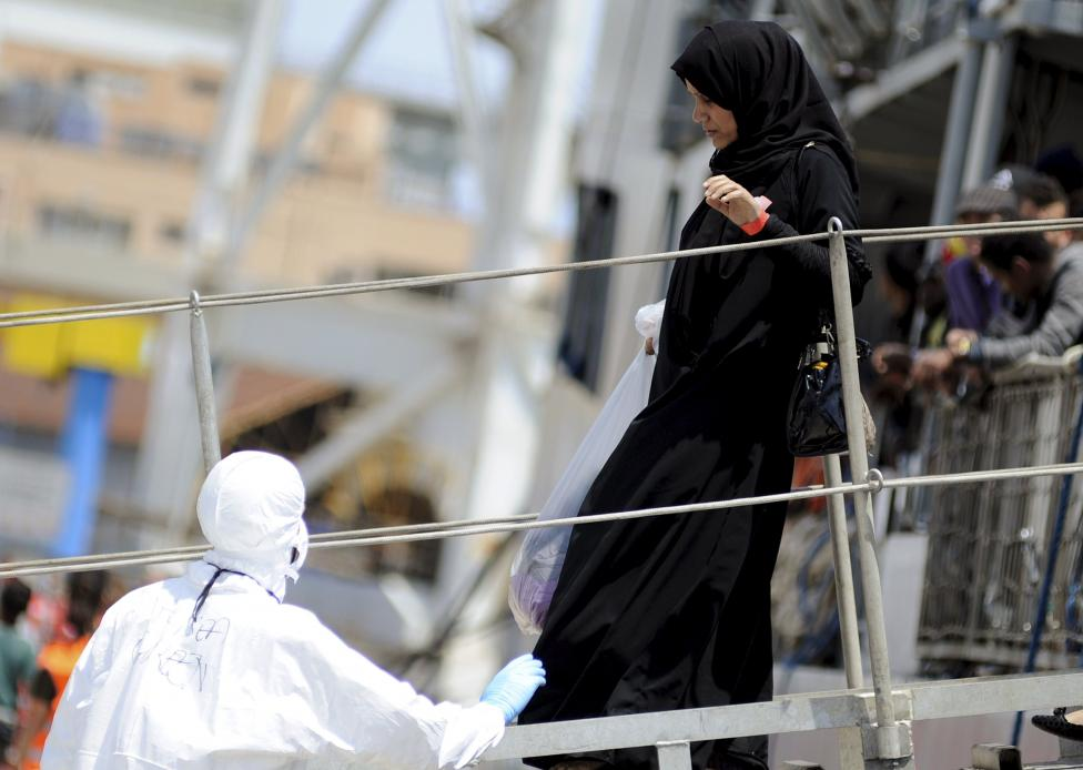A woman disembarks from the Irish navy ship LE Eithne in the Sicilian harbour of Palermo, Italy, May 30, 2015.  REUTERS/Guglielmo Mangiapane