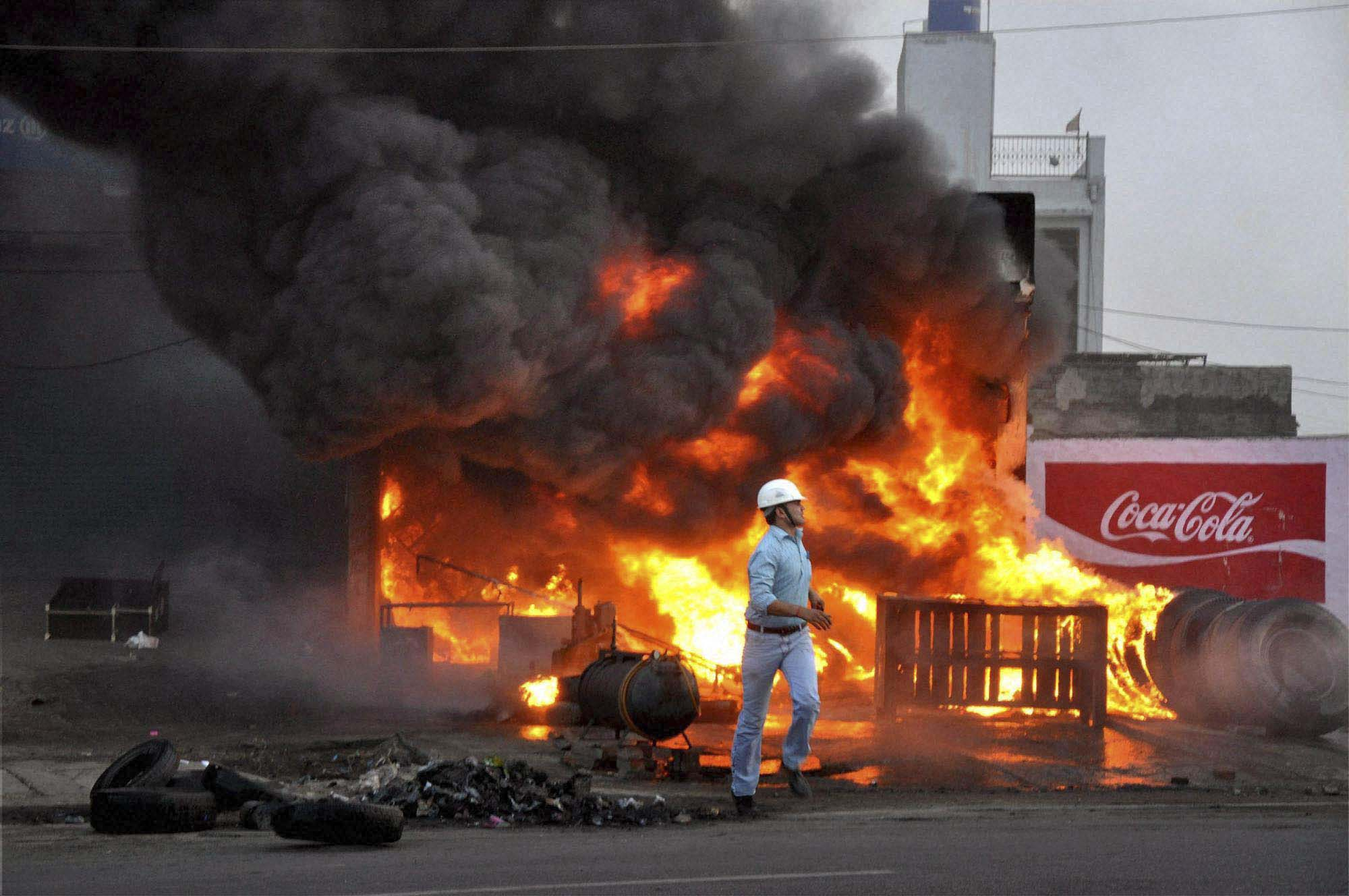 Mathura: A man running from a burning shop after a clash between two communities at Kosi Kalan in Mathura on Friday evening. PTI Photo (PTI6_2_2012_000026B)